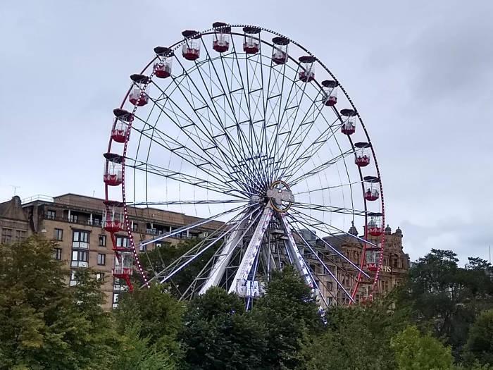 Red ferris wheel against cloudy sky