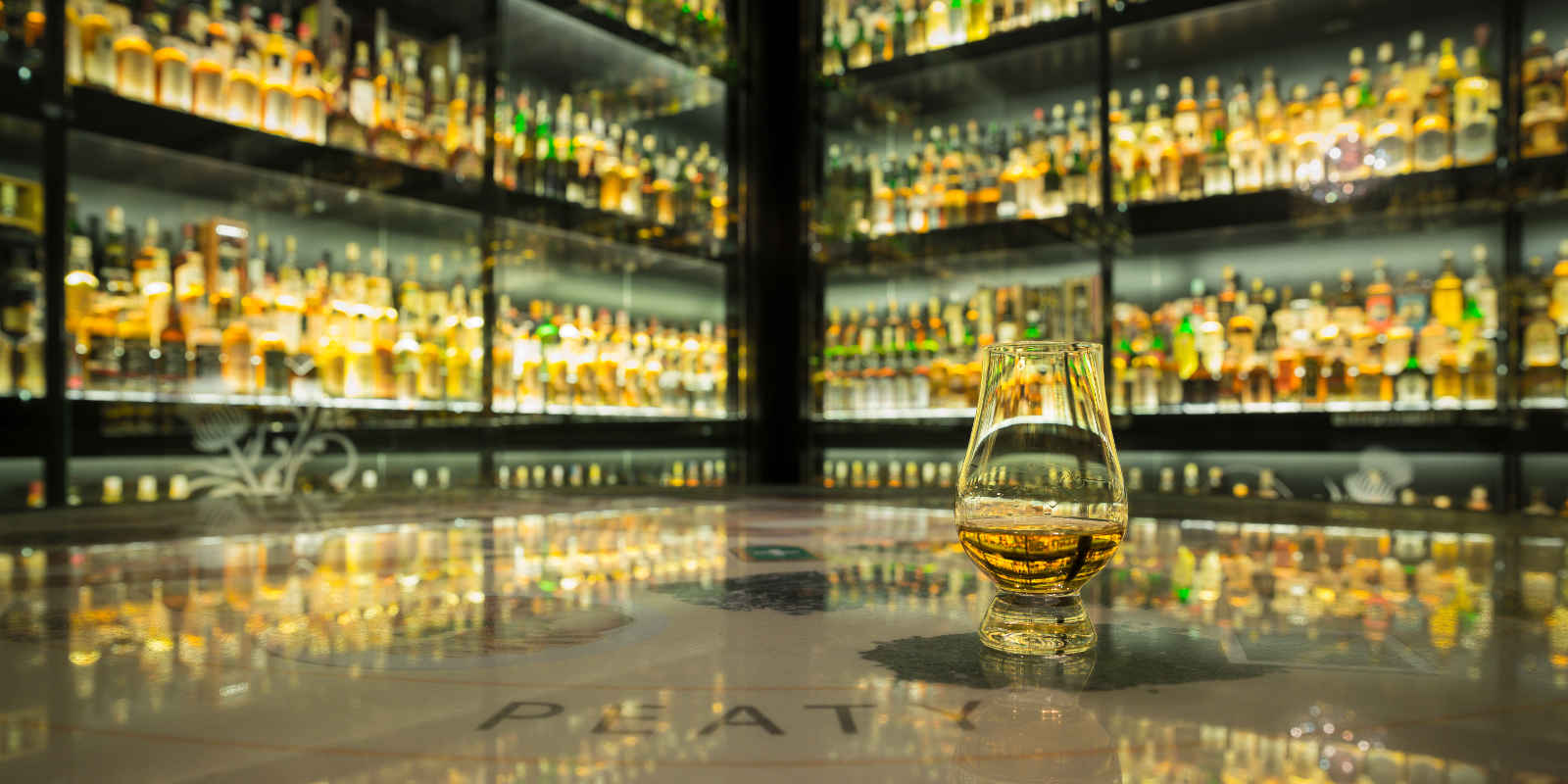 Glass of whisky on table with whisky collection in background