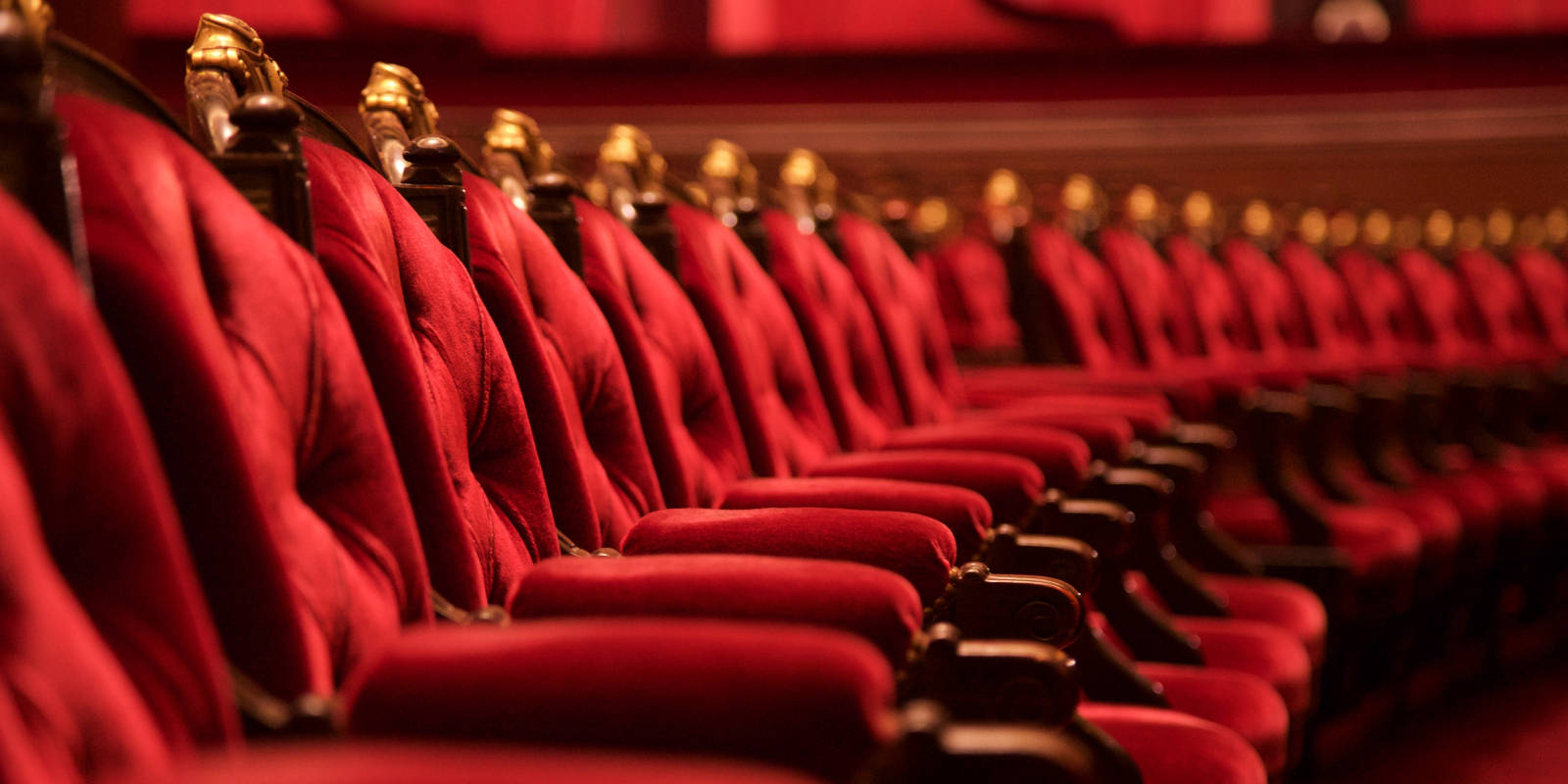 Row of red velvet seats in a theatre
