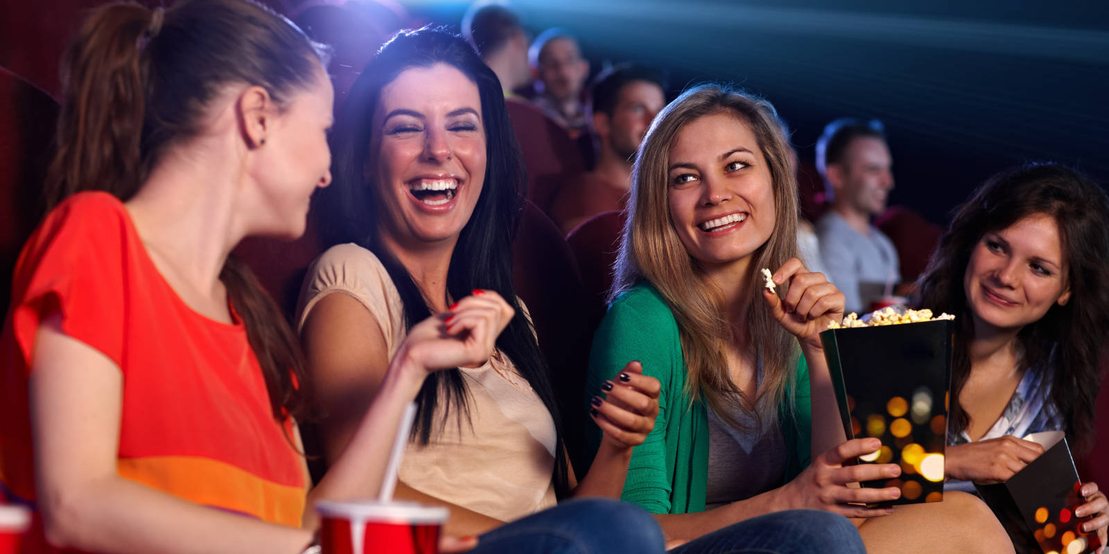 Group of women with popcorn and drinks in a cinema