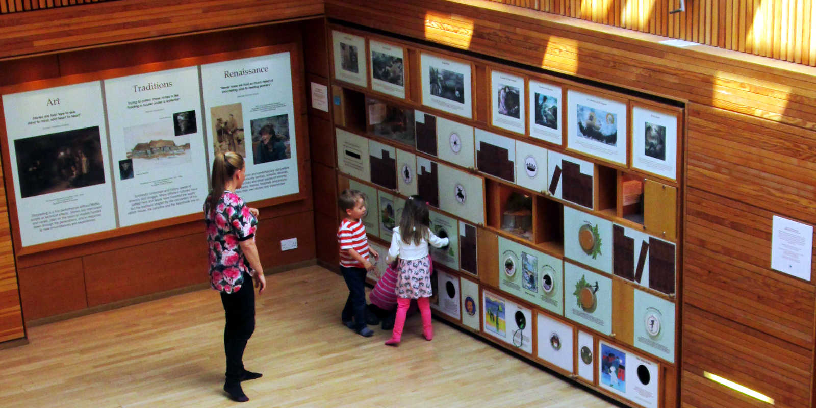 Mum and two children looking at Storytelling Wall